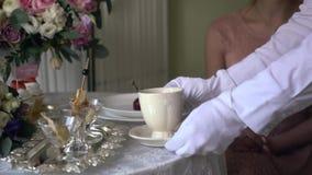 De kelner in witte handschoenen zet op de lijst voor het meisje een kop thee stock video