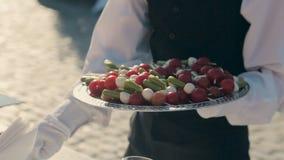 De kelner zet canape met kersentomaten en kaas op een plaat op catering stock video