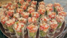 De kelner zet de stukken vissen in gedeelten met plantaardige salade op catering stock video