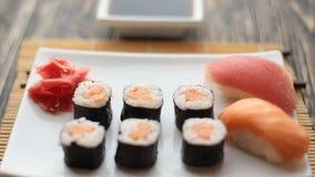 De kelner zet een plaat met sushi op de lijst stock videobeelden