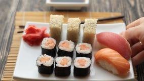 De kelner zet een plaat met sushi op de lijst stock video