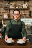 De kelner in zwarte schort houdt twee koppen van koffie Stock Foto