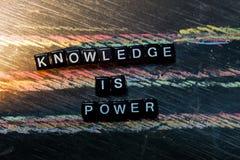 De kennis is Macht op houten blokken Kruis verwerkt beeld met bordachtergrond stock afbeelding