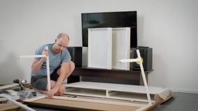 De kerel assembleert een meubilair zelf in een ruimte, die lange witte stralen installeren op een karkas van moderne lijst stock videobeelden