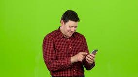 De kerel bekijkt de telefoon in de foto, en heeft pret Het groene scherm stock video