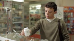 De kerel bekijkt de geneesmiddelen in het apotheekvenster stock footage