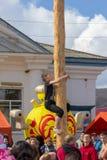 de kerel beklimt op een houten pool voor de prijs op de dag van feestmaslenitsa Stock Foto's