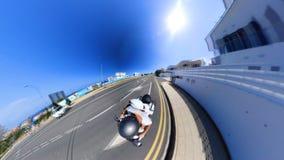 De kerel berijdt motor voorbij gebouwen in toevluchtstad stock videobeelden