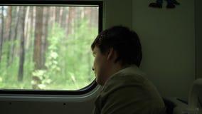 De kerel berijdt de trein en kijkt uit het venster, lettend op de bewegende voorwerpen buiten het venster Het reizen met familie stock videobeelden