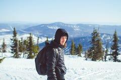 De kerel bevindt zich in de bergen in de winter Stock Foto's