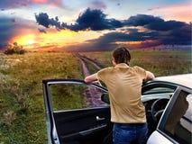 De kerel bevindt zich dichtbij auto en bekijkt de zonsondergang Stock Afbeelding