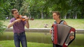De kerel bij de viool en het meisje op de harmonika spelen in het park De kerel bij de viool en het meisje stock foto's