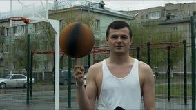 De kerel die een basketbal op zijn vinger op het open gebied spinnen stock video