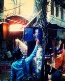 De kerel die electrocitykabel in de straat van Oud Delhi proberen te herstellen Stock Foto