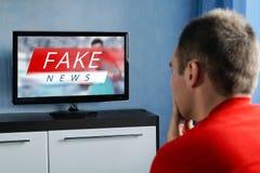 De kerel die op het valse nieuws op TV letten Corrupte journalistiek royalty-vrije stock foto