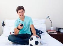 De kerel die van de tiener op een voetbalgelijke in televisie let royalty-vrije stock foto's