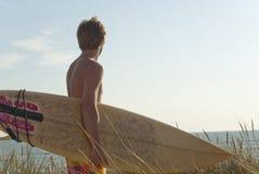 De kerel die van Surfer zich op duin bevinden Stock Afbeeldingen