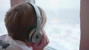De kerel die zich dichtbij het venster bevinden en aan muziek door hoofdtelefoons luisteren De zon` s stralen door het venster stock video