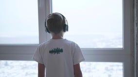 De kerel die zich dichtbij het venster bevinden en aan muziek door hoofdtelefoons luisteren De zon` s stralen door het venster stock footage