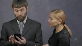 De kerel doorbladert de telefoon, rukt de vrouw zijn telefoon weg en begint te zweren familieruzie, huiselijk geweld 4K stock footage