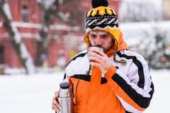 De kerel drinkt hete thee van thermosflessen in de winter Stock Afbeeldingen