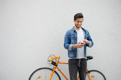 De kerel in een blauw denimjasje die zich op muurachtergrond bevinden jonge mens dichtbij oranje fiets Glimlachende student met z Royalty-vrije Stock Fotografie