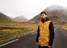 De kerel in een gele mantel loopt onderaan de weg in de bergen, royalty-vrije stock foto