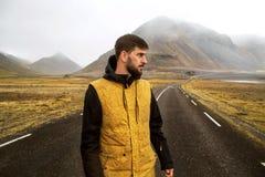De kerel in een gele mantel loopt onderaan de weg in de bergen, royalty-vrije stock afbeelding