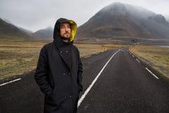 De kerel in een gele mantel loopt onderaan de weg in de bergen, stock fotografie