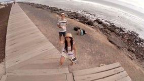 De kerel en een meisje lanceren een helikopter op de oceaankustCanarische Eilanden spanje stock videobeelden