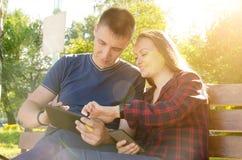 De kerel en het glimlachende meisje verzenden hun foto's naar vrienden via tablet stock foto