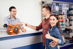 De kerel en het meisje betalen voor de aankoop van een kettingzaag royalty-vrije stock fotografie
