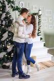 De kerel en het meisje bevinden zich op de achtergrond van de Kerstboom en onderzoeken elkaars ogen stock fotografie
