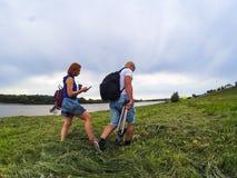 De kerel en het meisje in borrels en T-shirts gaan op hoog groen gras op de rivierbank met rugzakken Een vrouw heeft koffie en a stock foto