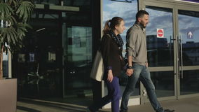 De kerel en het meisje gaan van de deur van de luchthaven uit stock video