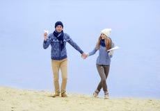 De kerel en het meisje lopen op de rivier royalty-vrije stock foto's