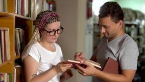 De kerel en het meisje spreken in de bibliotheek stock videobeelden