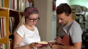 De kerel en het meisje spreken in de bibliotheek stock video