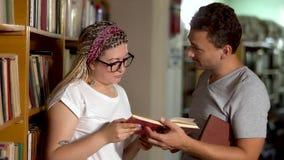 De kerel en het meisje spreken in de bibliotheek stock footage