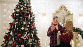 De kerel en het meisje verfraaien de Kerstboom stock videobeelden