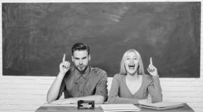 De kerel en het meisje zitten bij bureau in klaslokaal Correct antwoord op hun mening Het bestuderen op hogeschool of universitei stock afbeeldingen