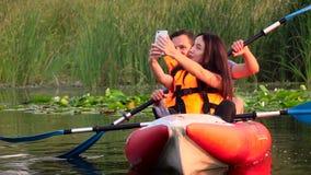 De kerel en het meisje zitten in een kajak en maken selfie Langzame Motie stock videobeelden