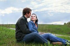 De kerel en het mooie meisje zitten op een gras Stock Foto