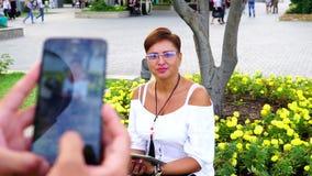 De kerel fotografeerde het meisje in het park stock footage