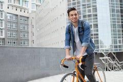 De kerel gaat naar stad op een fiets in jeansjasje jonge mens een oranje moeilijke situatiefiets Stock Fotografie