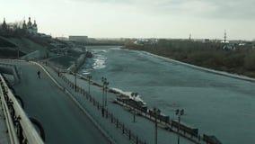 De kerel gaat op een skateboard op een helling naar de waterkant van de bevroren rivier stock videobeelden
