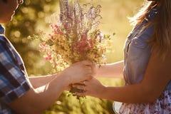 De kerel geeft het meisje in openlucht mooie wilde bloemen in de zomer stock afbeelding