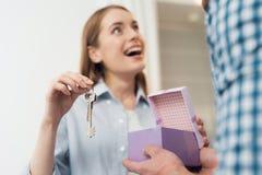 De kerel geeft zijn meisje een doos met een gift Het meisje ontving een gift de sleutel aan nieuwe huisvesting royalty-vrije stock foto