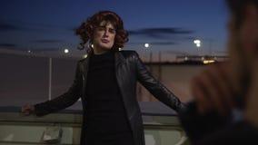 De kerel gekleed als vrouw die met samenstelling, zwarte kleren en pruik dragen, zingt buiten stock video