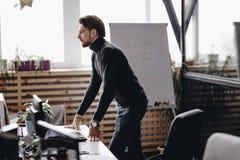 De kerel gekleed in toevallige de klerentribunes van de bureaustijl bij bureau in het moderne bureau dat met moderne kantoorbenod stock afbeeldingen